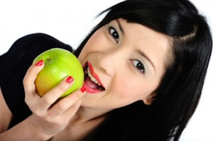 Young asian girl eating apple